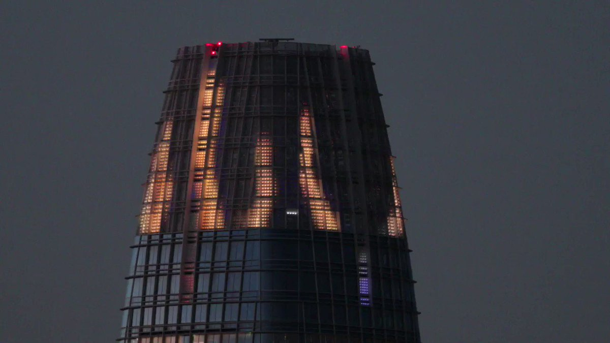 The top of the Salesforce Tower is illuminated with a video of clapping hands and prayer flags in support of medical workers and first responders fighting #COVID19.