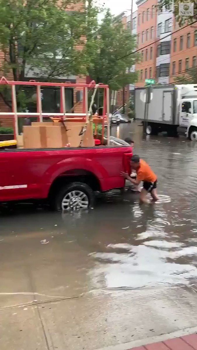 Residents push a truck through floodwaters in Hoboken, New Jersey, as Tropical Storm Fay brought downpours to the region. The storm has since weakened.