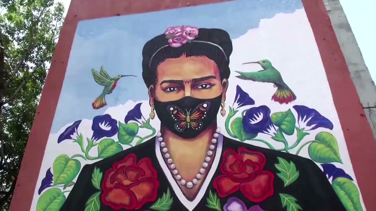 On the anniversary of Frida Kahlo's death, fans of the artist painted a mural with her signature unibrow and indigenous dress as well as a face mask