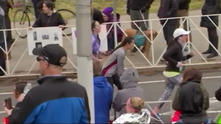 The heartwarming moment when two runners help an exhausted competitor cross the finish line.