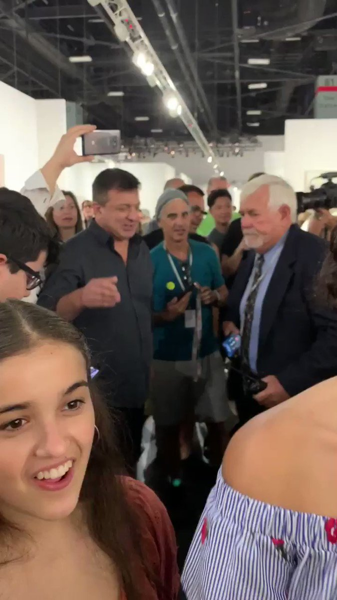 a guy at Art Basel pulled the banana worth $120k off the wall and ATE IT!!!! here's him being escorted out