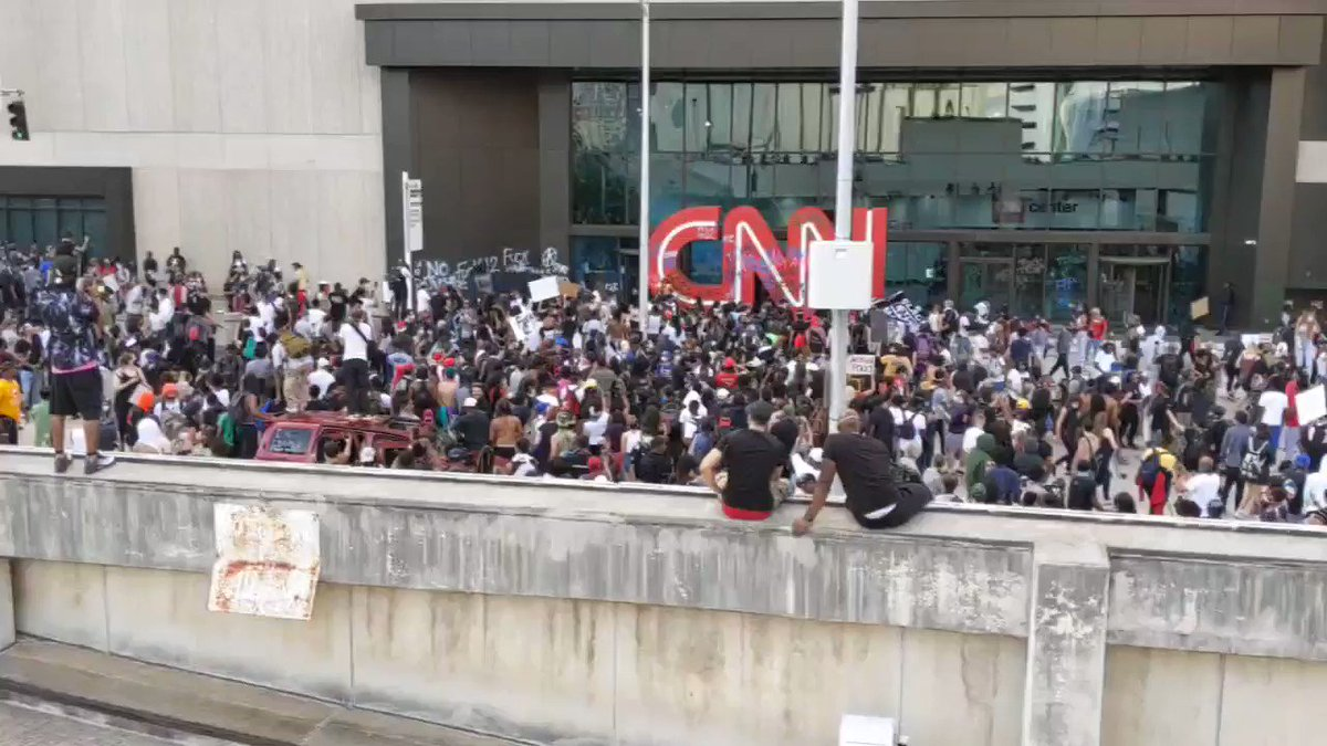Glass getting broken outside the main entrance to CNN's Atlanta headquarters; protesters cheer