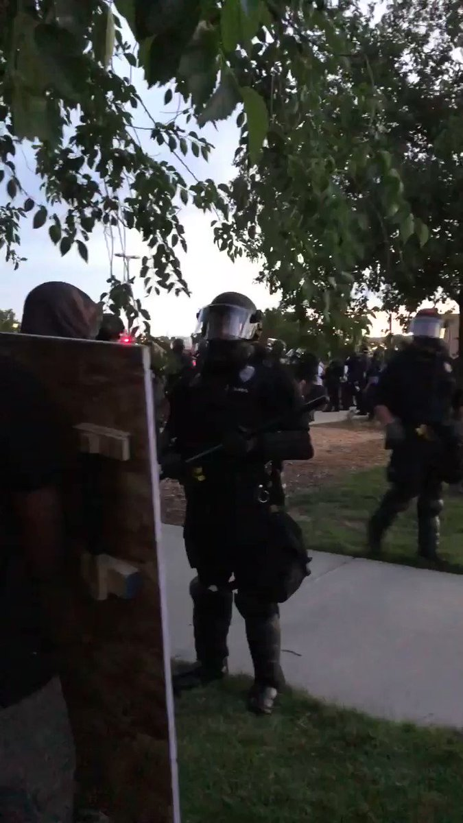 The police push people out of most of the park and form a wall. One violinist leaves the stage and gets on top a car and starts playing to the crowd that had been pushed out first.