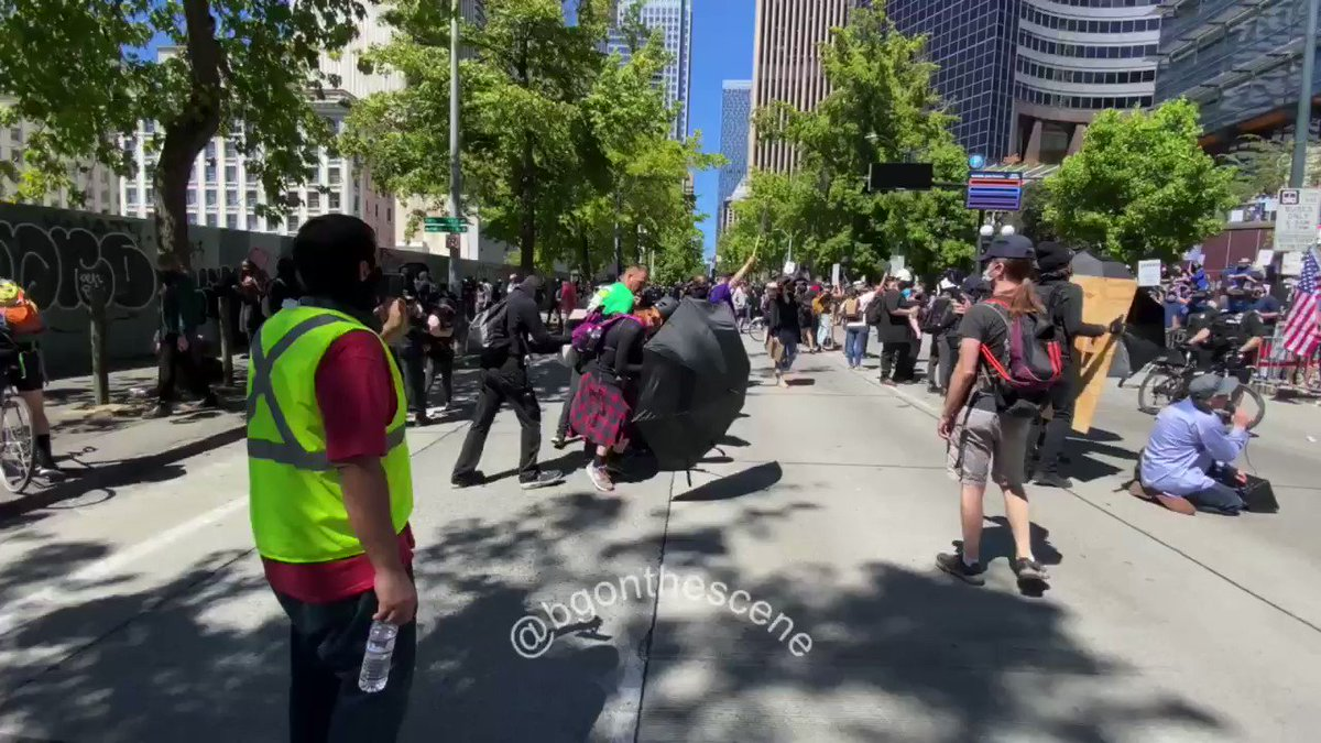 #Antifa black bloc assault a street preacher outside Seattle city hall today. They try to stop press from recording.