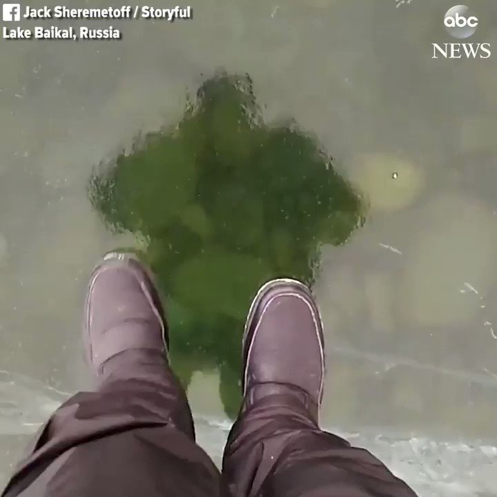Stunning video shows a man walking across a crystal-clear frozen lake in Russia.
