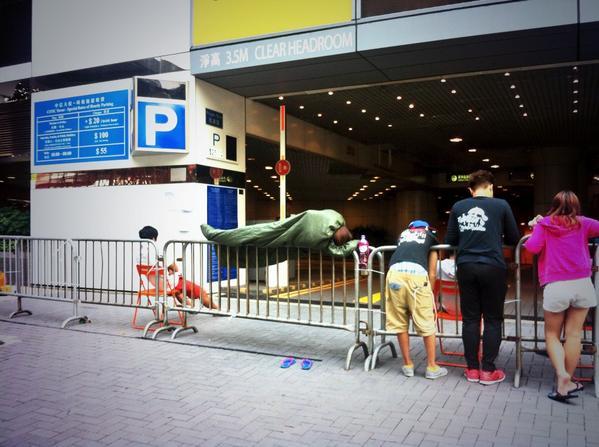 為了守護中信大廈出入口,這位示威者徹夜睡了在鐵馬之上。她這身堪比小龍女的功夫是怎樣練成的呢?  #傘花革命 #occupyhk #UmbrellaMovement #umhk http://t.co/wVhs5iJXK1