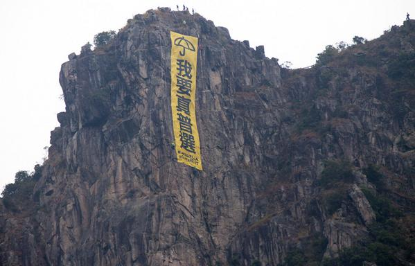 """Umbrella banner now hanging off Hong Kong's iconic Lion Rock! Says """"We Want Universal Suffrage!"""" #UmbrellaMovement http://t.co/rALk40TgTc"""