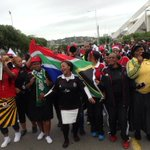 Soccer fans singing outside the Moses Mabhida Stadium ahead of the funeral service #SenzoMeyiwa #SABCNews http://t.co/oMj8ufgfny