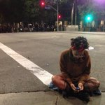 Protester sits on the road in anticipation of arrest by LAPD. #MichaelBrown #Ferguson protests, day 2. http://t.co/pCeaR2IGkp