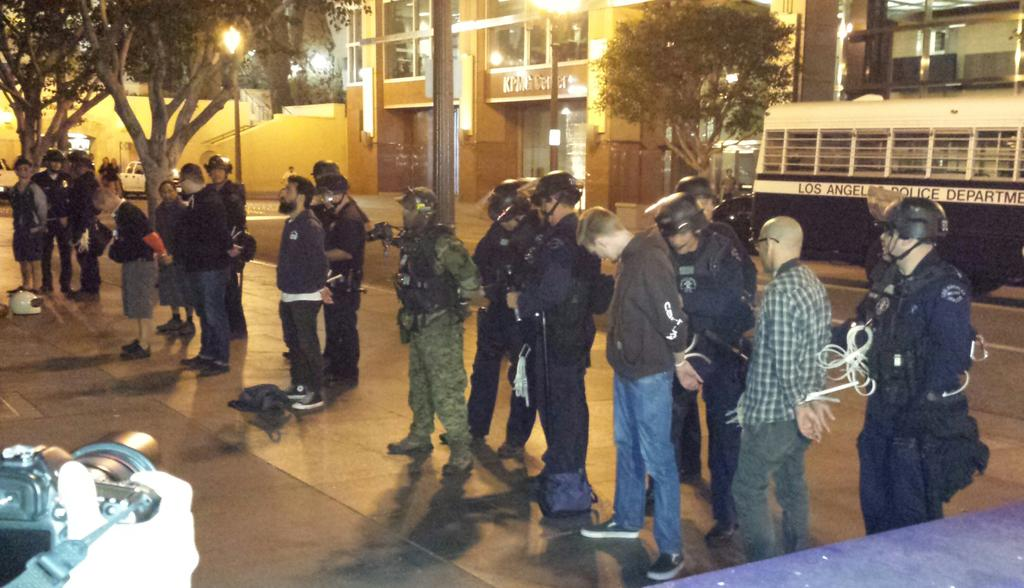 #Ferguson protesters being lined up and cuffed in downtown L.A. Will be put on LAPD bus and taken to jail. http://t.co/sYz5BOcNyL
