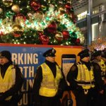 """A ring of police defending the Christmas tree. Ten feet away, circle of protesters chanting, """"No justice no peace!"""" http://t.co/uhdUV3NODZ"""