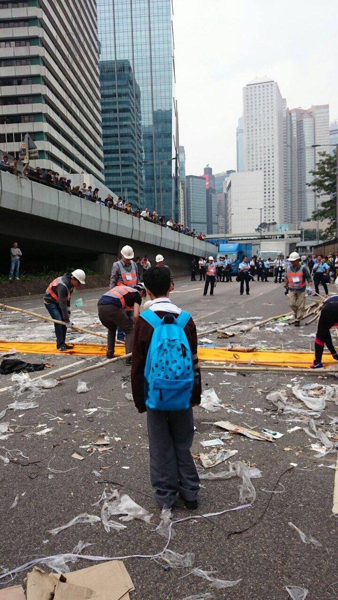 Benson Tsang: (朋友傳來這相片,希望我代傳出去。) 昨天金鐘清場,這位中學生茫茫然看著成年人清走佔領區的東西。 作為成年人的你,看見這張相片有什麼感覺?請睜開自己的眼睛,政府拆走了什麼?而成年人又留下什麼給我們的下一代? http://t.co/5G74YhG21z