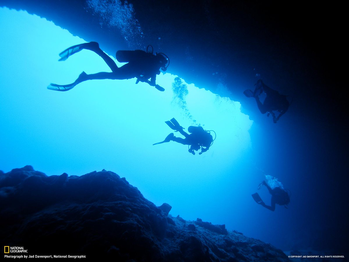 Divers explore an underwater cave system on Andros Island in the Bahamas