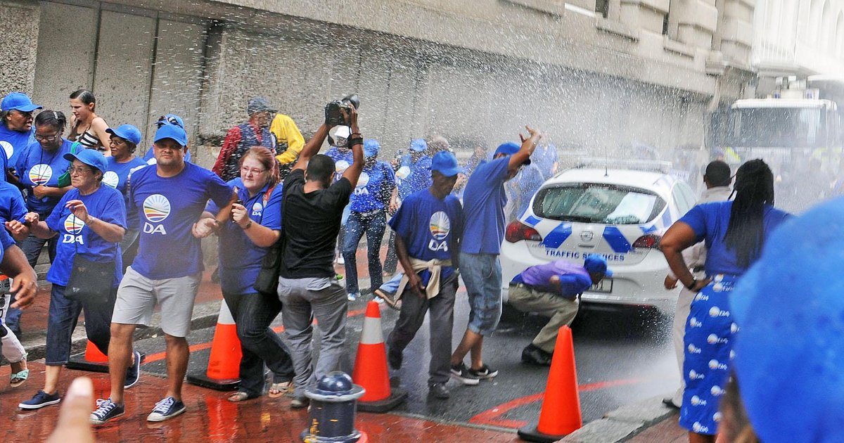 DA supporters get blasted by a water cannon in Cape Town's CBD ahead of #SONA2015 . Photo:Tracey Adams @TheCapeArgus http://t.co/ssntoN7cq7