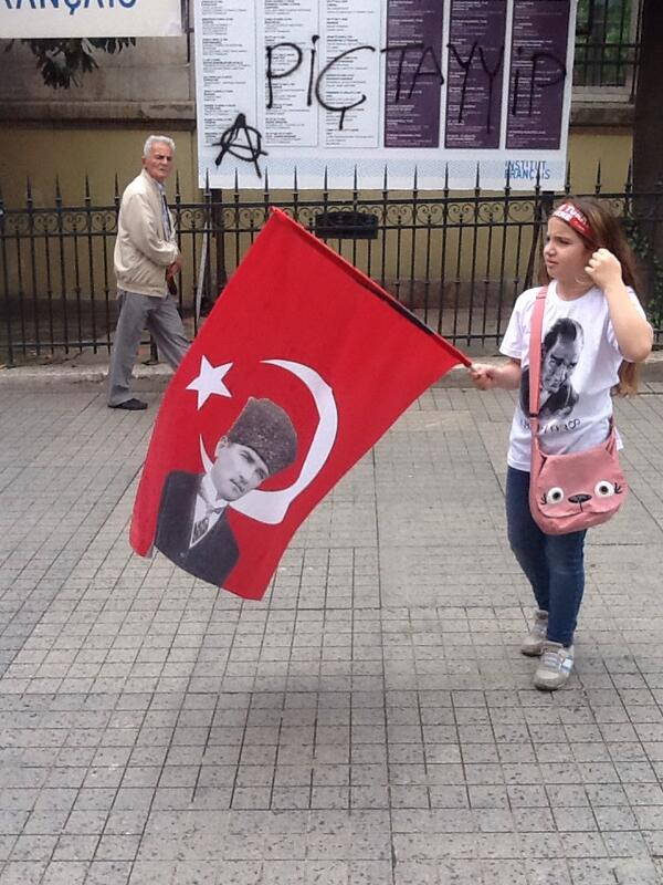 MT @AnshelPfeffer Girl carries Kemalist flag in #Istanbul; graffiti in background curses PM Erdogan #occupygezi http://t.co/wo9bLTusru