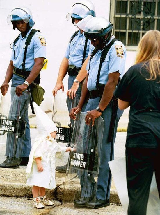 A small white boy touches the riot shield of a black state trooper at a Ku Klux Klan rally in Atlanta, 1992. http://t.co/ax06oAISyi