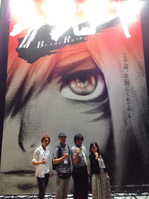 三杜シノヴ描きおろし特大ポスター前(瞳にアメがいる!)で熱風海陸ブシロードチームの記念撮影。アメ役の潘めぐみさん、スオウ