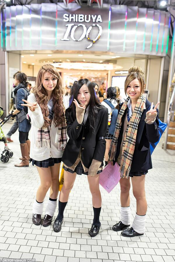 Three friendly japanese schoolgirls in uniforms and loose Yes style japanese fashion