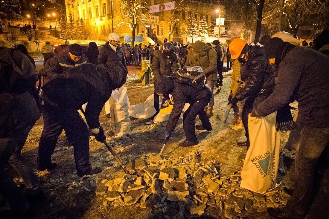 Как строят баррикады — сотни людей с ломами и лопатами очищаюю от льда тротуары и набивают эти мешки для баррикад. http://t.co/ayZNu0iTpP