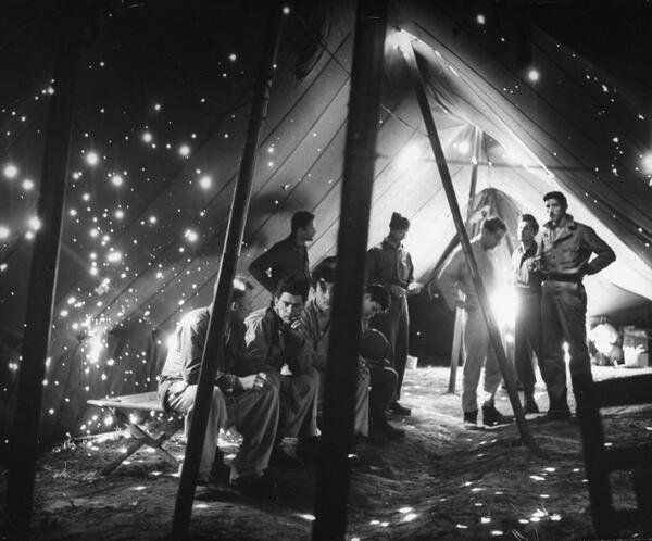 A holy tent, soldiers rest in a shrapnel ridden tent after a German artillery strike on the Anzio beach head 1944. http://t.co/xMoHXuSiMu