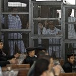 Al Jazeera journo @PeterGreste  + colleagues inside the defendants cage during their trial in Cairo (@GettyImages) http://t.co/xZzOASS8VV