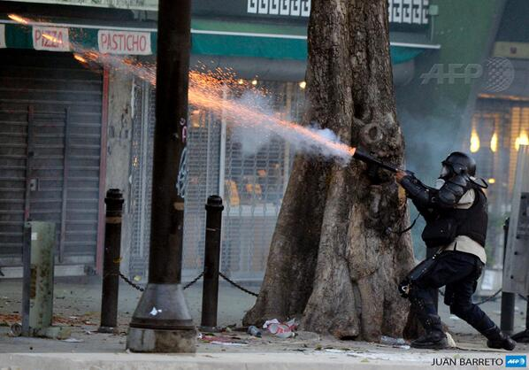 A National Police member shoots tear gas at opposition activists in Caracas, Venezuela, by @jbarreto1974 http://t.co/etB12nlNmI