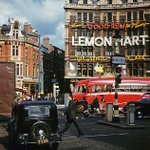 Gent crossing Cambridge Circus, 1957. Traffic like today. Love the gorgeous bus & moped girl with no helmet! #London http://t.co/N5LFb9xbc2