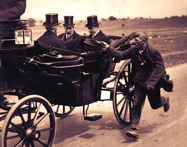 """ملك بريطانيا ومرافقوه في عربته الملكية عام1920م ويجري خلفهم هذا""""الشحاذ"""" ويرفع قبعته ليتصدقوا عليه #غرد_بصوره http://t.co/JKkaNt8ZQL"""