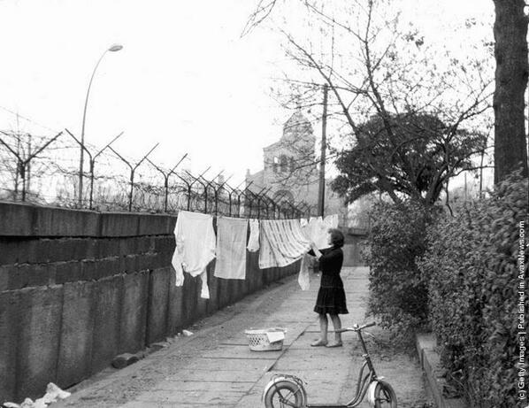 A German women hangs clothing out to dry on a line strung between a tree and the Berlin Wall, Germany, 1963 http://t.co/VWhgiQ59dy