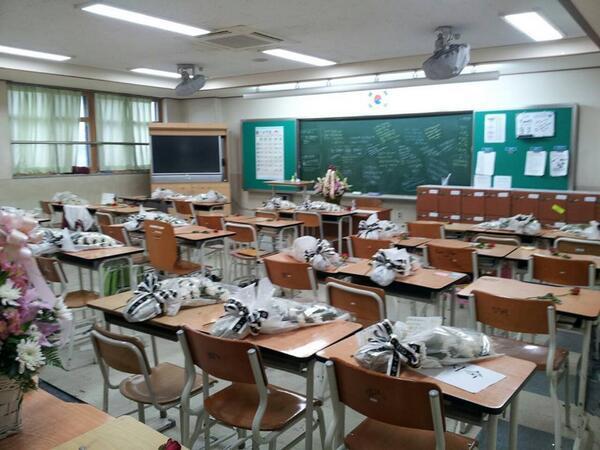 韓国旅客船沈没事故 静まり返った教室の机に並べられた花束の写真。これは辛い。