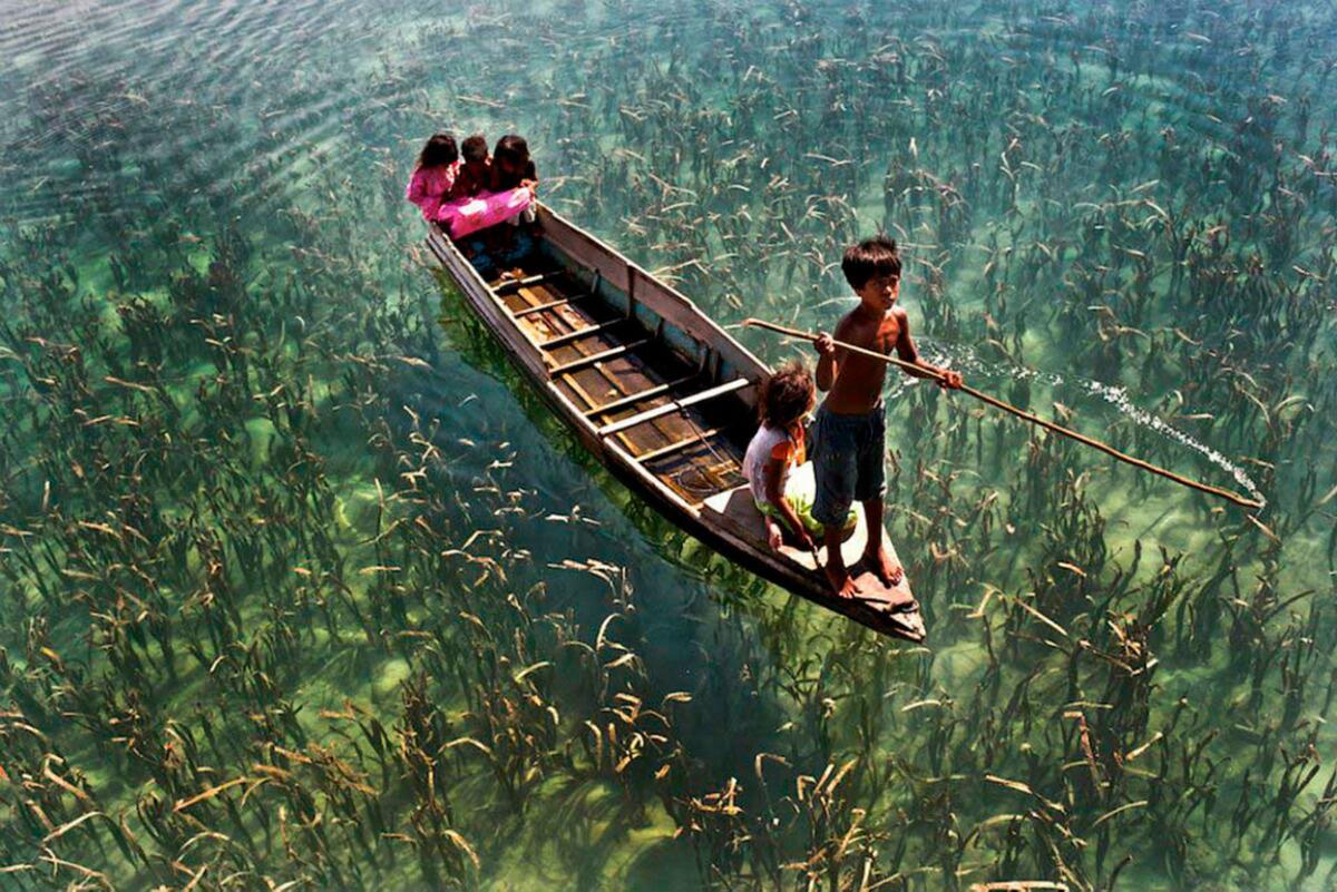 Children riding on a boat on a crystal clear lake in Sabah, Malaysia. http://t.co/IxWw2JyjP4