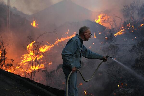 Dramatic image of 72-year-old fighting #CocosFire with garden hose by @RickLoomis via @latpix http://t.co/TBntjgAnz3 http://t.co/pdpUnPIOCX