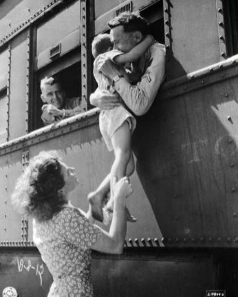 A soldier's wife hoists her son up to a train window for one last good-bye hug from his dad. 1940s. http://t.co/9sS787rCI1