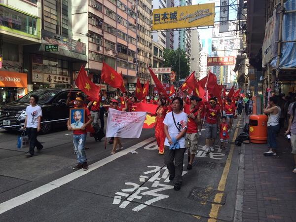 """跟在六四游行后的是越南人组成的方阵,他们抱着胡志眀照片,举着""""西沙是越南的""""等横幅,昂首走来。。。令我感动!当然不是被越南感动,我是被香港感动!香港警察保护越南人在中国的领土香港抗议中国,何其了不起的中国香港!东方之珠,我的爱人! http://t.co/pFQWIZXE6T"""