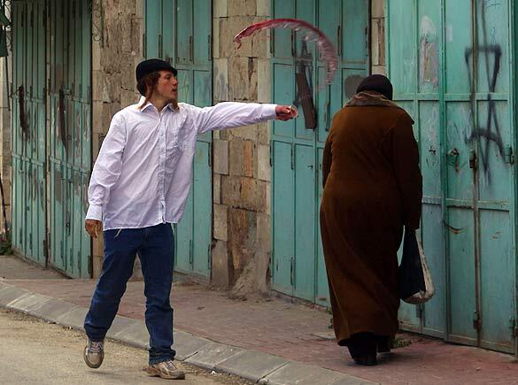 A jewish settler throwing wine at a Palestinian Woman http://t.co/opLHsrUewI