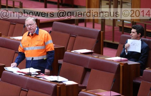 """#seemsfair Sen. Ludlum holds up a sign """"SRSLY""""behind Sen. Macdonald @murpharoo @GuardianAus #politicslive http://t.co/0DAiiYp57d"""