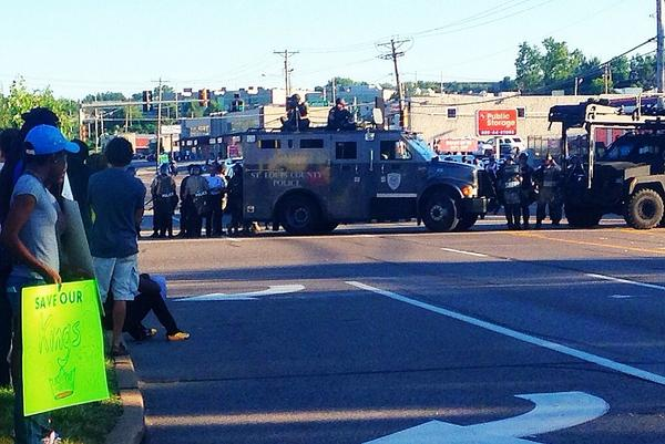 Police in armored trucks/riot gear in #Ferguson unsuccessfully trying to get demonstrators to leave. #MichaelBrown http://t.co/hJKwVVdaKh