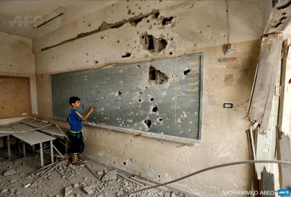 A Palestinian boy writes on a shrapnel-riddled blackboard at a school in Gaza City (via @afp) http://t.co/XvbnQFSmUd