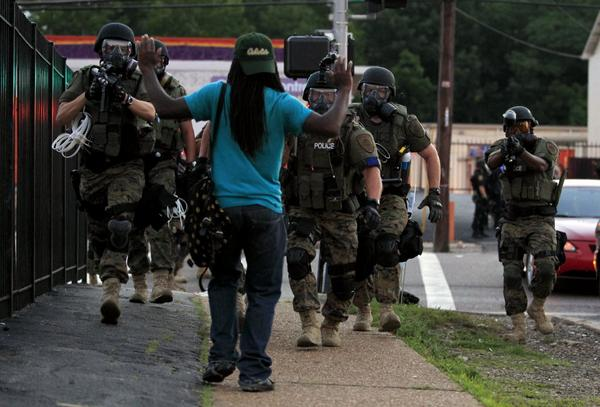 Police in riot gear approach a man with his hands raised in #Ferguson Monday | AP Photo http://t.co/e5c0FKngO7 http://t.co/AkiEpgAuzI