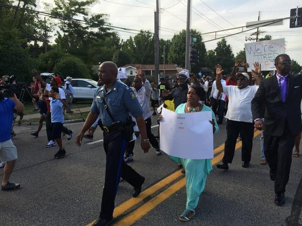 Capt. Ron Johnson of the Missouri Highway Patrol walks along with the Ferguson march. Compare this to Wednesday. http://t.co/Vtezu4MuHk