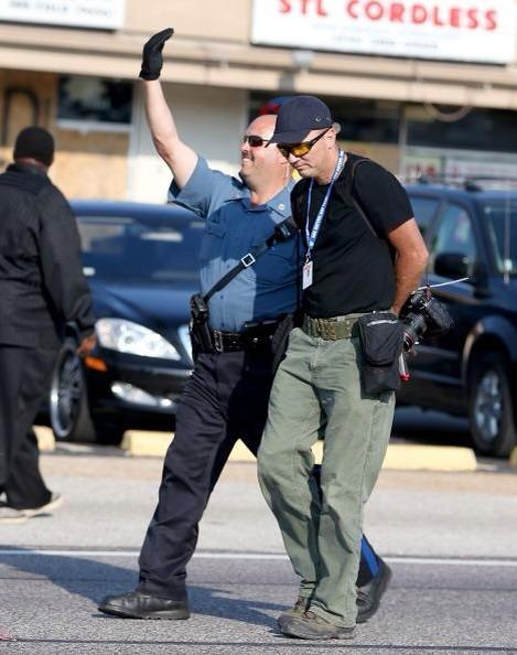 WTF RT @onekade Look at how happy this cop is arresting a journalist in #Ferguson http://t.co/t8LS2jBBYt v @mattgallowaycbc
