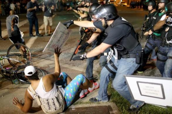 "NOT OK! RT: ""@Bipartisanism: This protestor was holding a sign. Police respond with a shotgun in her face. #Ferguson http://t.co/yklsLMWGew"""