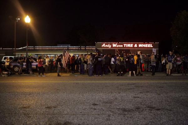 Crowd across from police department has swelled to about 100 people. #ferguson (photos: @aymanndotcom) http://t.co/LADdtKUVTI