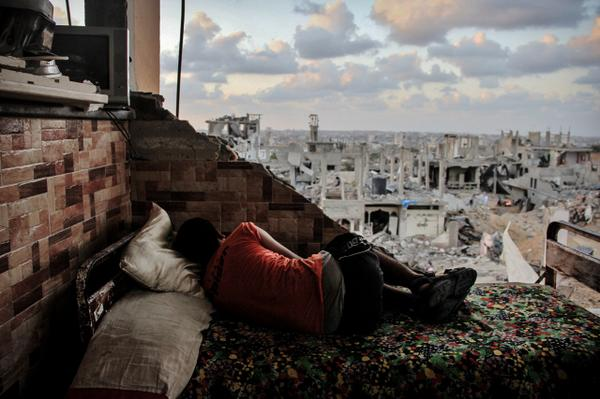 A boy sleeps amid the rubble of his destroyed house in Gaza Strip. Photo by Ahmed Hjazy #photography http://t.co/WXsj2fRJV8