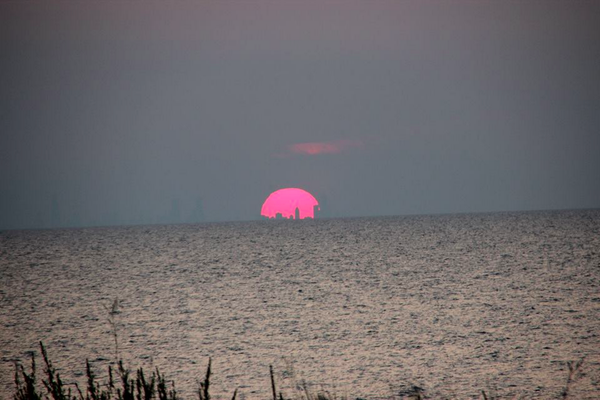 Sunset over Lake Michigan August 7th. The silhouette of Chicago inside the sun. http://t.co/PUsr3b161A
