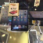Retina iPad Mini in Times Sq window has fake screen with anachronistic skeuomorphic interface, battery at 1%.