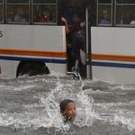A boy plays at a flooded street in front of a passing bus as Mario battered Manila; Erik de Castro/ Reuters http://t.co/TgFuwOomlR