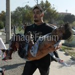 An Afghan man carries a wounded man at the site of a suicide attack in Kabul. http://t.co/g6xz8PNv4d