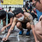 A protester washing off graffiti on the floor at #UmbrellaRevolution http://t.co/bzn7mqOUdv