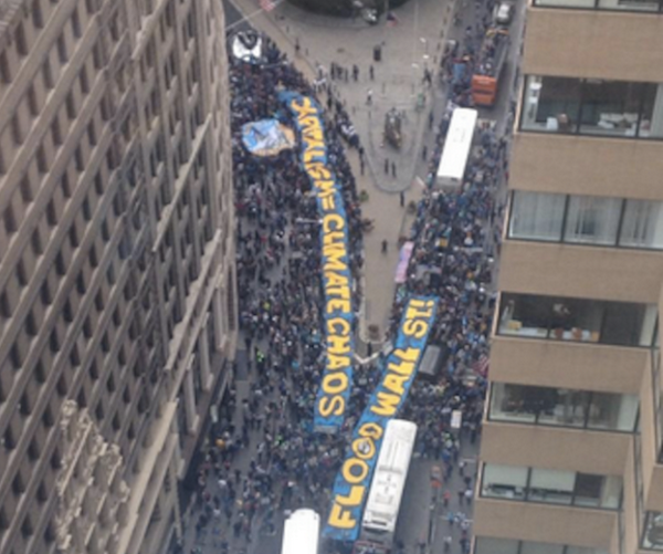 Aerial view of #FloodWallStreet's MASSIVE banner & sit-in on Broadway. Crowd surrounds the Wall St Bull. http://t.co/7IuOsu2k5G